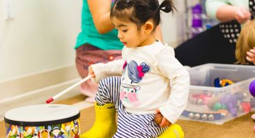 girl-playing-drum-living-montessori