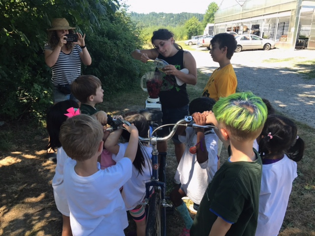 A female camp instructor is taking a picture of kids getting ready to enjoy a nice smoothie from an organic farm after a long bike ride.