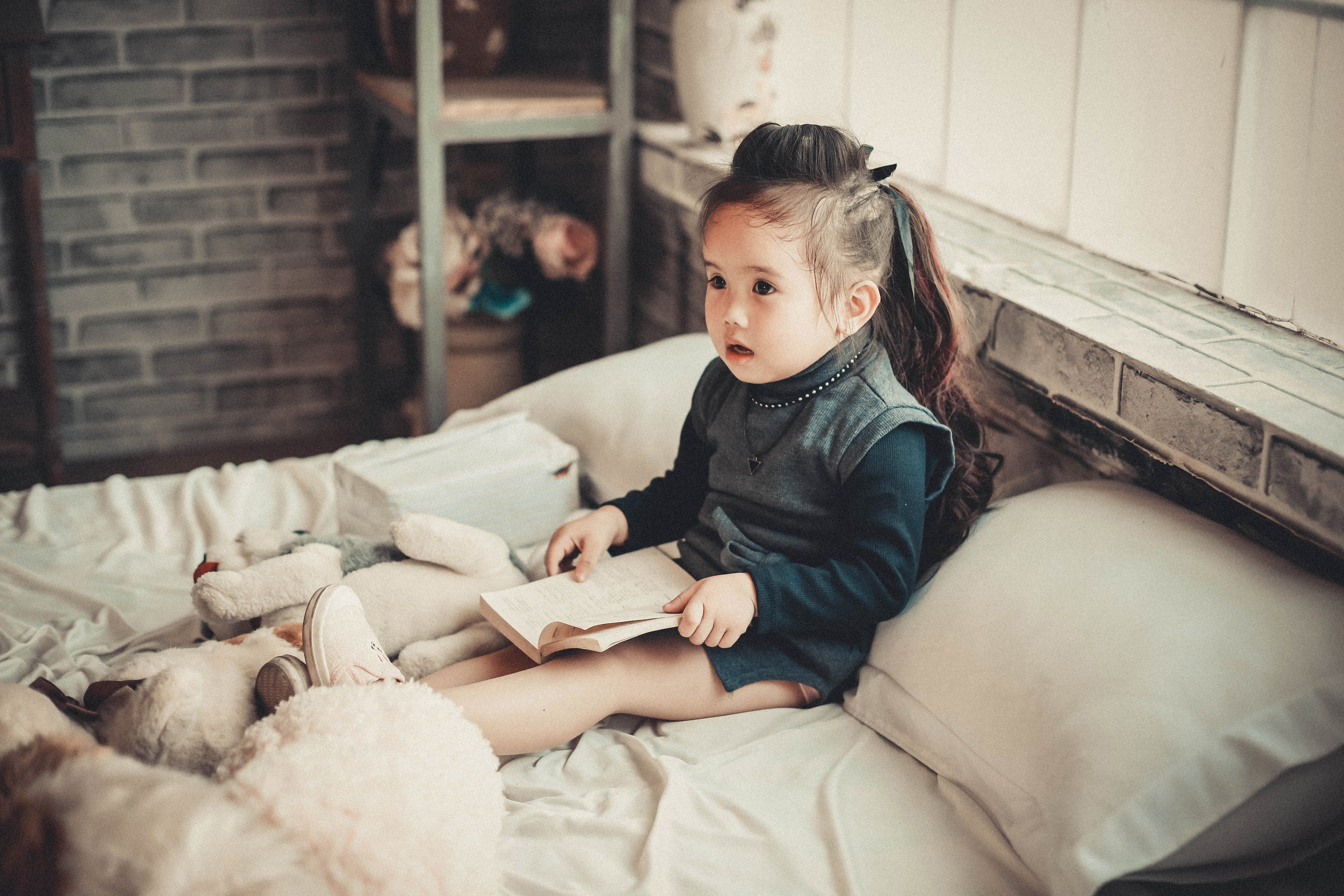A little girl sitting upright in bed reading like an adult.