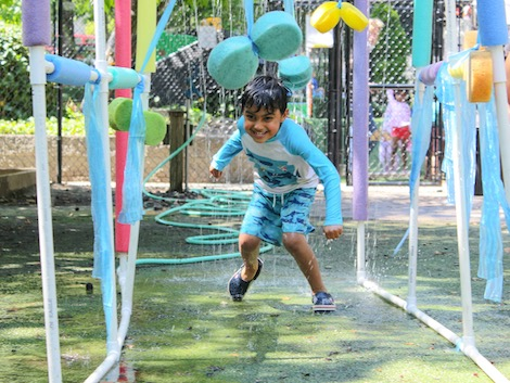 Soaked, Determined Camper Runs Through A Sprinkler And Sponge Maze On A Warm Day